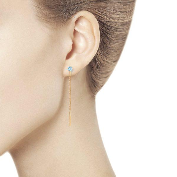 Naise kõrvas rippuvad kuldkõrvarõngad siniste topaasidega kaubamärgilt Sokolov
